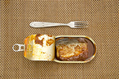 Open canned fish metal can and fork Royalty Free Stock Image