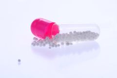 Open capsule. Pink capsule isolated on white background Stock Photos