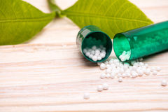 Open capsule with small white balls and green leaf Royalty Free Stock Images