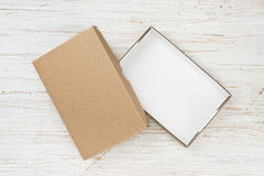 Open cardboard box with cover on wooden table, above view Royalty Free Stock Photos