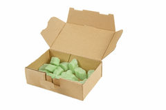Open cardboard box with green packaging chips Royalty Free Stock Photography