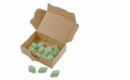 Open cardboard box with green packaging chips Stock Photos