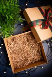 Open Carton Present Box With Ribbon On Blue Background Surrounded By Decorative Lights. Royalty Free Stock Photography