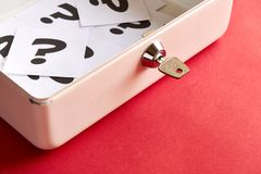 Open cashbox with question marks and key on pink background stock photo