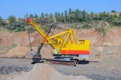 Open cast mine. Big yellow excavator extracting iron ore in opencast mine Royalty Free Stock Image