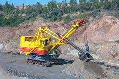 Open cast mine. Big yellow excavator extracting iron ore in opencast mine Stock Photography