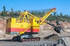 Open cast mine. Big yellow excavator extracting iron ore in opencast mine Royalty Free Stock Photography