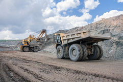 Open cast mine. Big yellow excavator extracting iron ore in opencast mine and loading heavy truck Stock Images