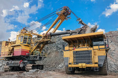 Open cast mine. Big yellow excavator extracting iron ore in opencast mine and loading heavy truck Stock Photography