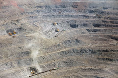 Open cast mine. Close up of quarry with excavators and locomotives extracting iron ore Stock Images