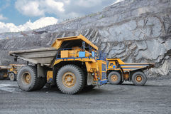Open cast mine. Picture of big yellow heavy trucks in open cast mine Royalty Free Stock Image
