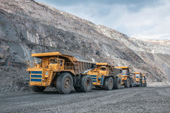 Open cast mine. Picture of big yellow heavy trucks in open cast mine Stock Images
