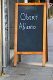 Open. Chalkboard with the word open in Catalan and Spanish stock image