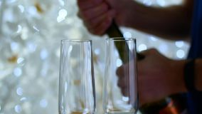 Open the champagne. Two glasses in the foreground, and a New Year`s garland in the background.  stock video