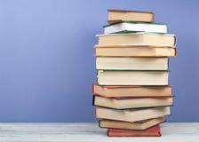 Open che impila libro, i libri variopinti della libro con copertina rigida sulla tavola di legno e fondo blu Di nuovo al banco Co Fotografia Stock