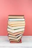 Open che impila libro, libri variopinti della libro con copertina rigida sulla tavola di legno, rosso, fondo rosa Di nuovo al ban Fotografia Stock Libera da Diritti