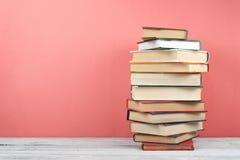Open che impila libro, libri variopinti della libro con copertina rigida sulla tavola di legno, rosso, fondo rosa Di nuovo al ban Immagini Stock Libere da Diritti