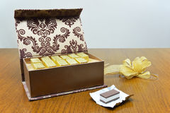 Open chocolate box. And chocolate wrapper with chocolate on wooden table Stock Image