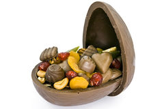 Open Chocolate Easter egg. Chocolate Easter egg full of dried fruits, chocolate candy and nuts royalty free stock photo