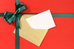 Open Christmas or birthday card, green gift ribbon bow on plain red paper background Royalty Free Stock Images