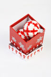 Open Christmas box with red and white christmas ball inside. Red Christmas filled box with red and white Christmas decoration on white background. Open Christmas Stock Photo