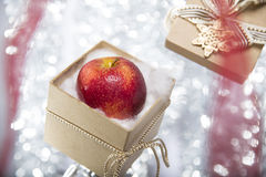 Open christmas gift box with an apple Stock Photography