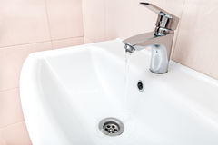 Open chrome faucet water flow in the wash basin. Open chrome faucet water flow in the ceramic wash basin in the bathroom with a beige tile on wall Stock Image