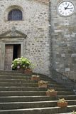 Open church. Stairs with flowers leading to an open door of a Tuscany church with a clock tower Stock Photos
