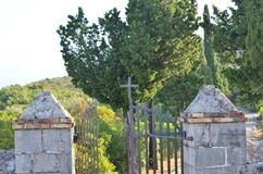 Church open gate. Open church iron gate with lush trees behind it stock image