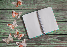 Open clean notepad and homemade paper butterfly on a wooden vintage background. Top view, free space for text. Royalty Free Stock Image