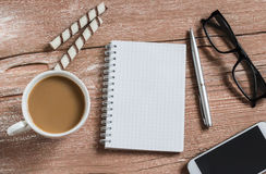 Open a clean Notepad, pen, glasses, phone, cup of coffee and biscuits. The office coffee break. Stock Image