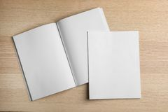 Open and closed blank brochures on wooden background, top view. royalty free stock photos