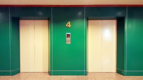 Open and closed chrome metal office building elevator doors realistic photo. Lift transportation floor to floors with push switch. For up and down. Green wall stock image