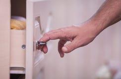 Hand opens a cupboard. Open closet door, male hands opening closet door Royalty Free Stock Photography