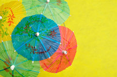 Open cocktail umbrellas. Displayed on a yellow background royalty free stock photo
