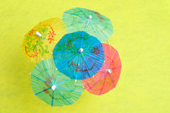 Open cocktail umbrellas. Displayed on a yellow background royalty free stock photos