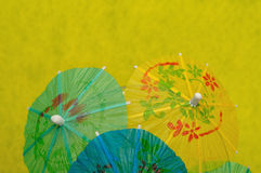 Open cocktail umbrellas. Displayed on a yellow background stock images