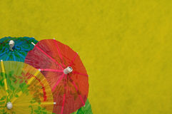 Open cocktail umbrellas. Displayed on a yellow background royalty free stock images