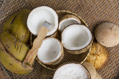 Open coconut with coconut peel. On bamboo mat Stock Photo