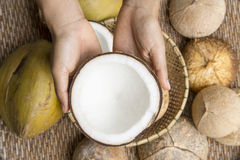 Open coconut with coconut peel. And hand on bamboo mat Stock Photography