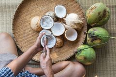 Open coconut with coconut peel. And hand on bamboo mat Stock Photos