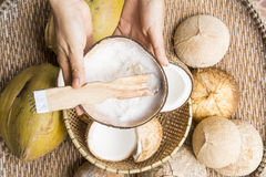 Open coconut. With coconut peel and hand on bamboo mat Royalty Free Stock Image