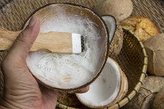 Open coconut. With coconut peel and hand on bamboo mat Stock Photography