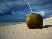 Open coconut on tropical beach and by water Royalty Free Stock Image