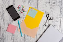 Open colored envelope blank sheet paper sticky notes ballpoint clips notepad scissors smartphone lying retro vintage royalty free stock image