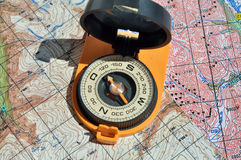 Open compass on the maps. Stock Photos