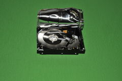 Open computer hard disk drive. Computer hard disk drive with casing open on green background Royalty Free Stock Photos