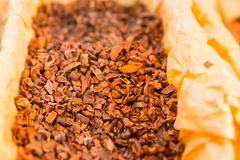 Open container of raw cocoa pieces for sale Royalty Free Stock Photo