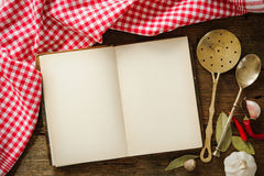 Open cookbook with kitchenware. On checkered tablecloth Royalty Free Stock Image