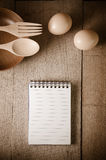 Open cookbook and kitchenware on wooden background Royalty Free Stock Photography